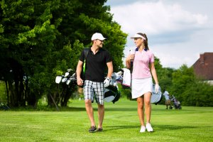 Young sportive couple playing golf on a golf
