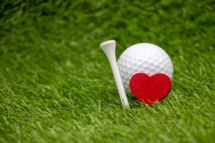 Golf ball with red heart and tee for golfer